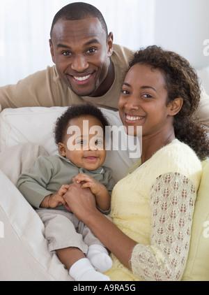 Porträt von Eltern und Baby auf sofa - Stockfoto