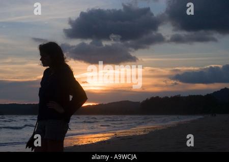 Silhouette eines Mädchens bei Sonnenuntergang - Stockfoto