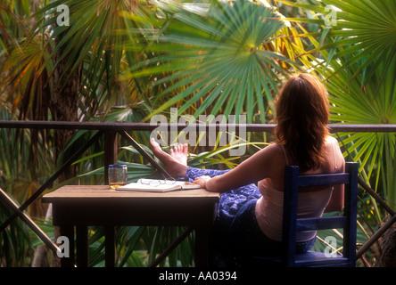 Frau sitzt am Tisch, umgeben von Dschungel in der Nähe von Tulum Quintana Roo Mexiko Modell und der Eigenschaft - Stockfoto