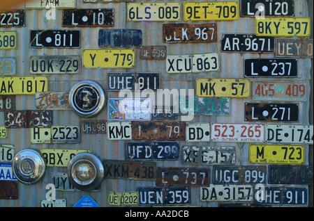 Alte Kfz-Kennzeichen, Gwalia, Western Australia. Mehrere verschiedene Dateien auf der Seite eine Wellblech-Garage. - Stockfoto