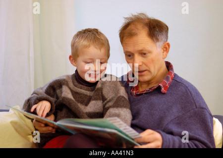 Vater liest seine wenig fünf Jahre alten Jungen ein Bilderbuch Bilderbuch