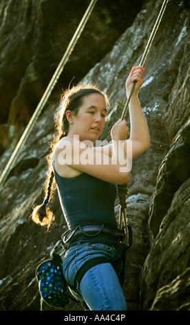 Ein junge Frau Kletterer macht einen Seil klettern Aufstieg über Palm Beach Pittwater Sydney Australia - Stockfoto