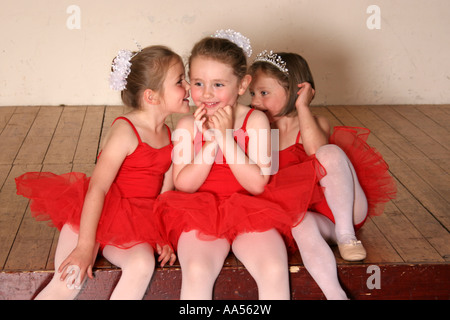 Drei junge Ballerinas Flüstern miteinander auf der Bühne. - Stockfoto