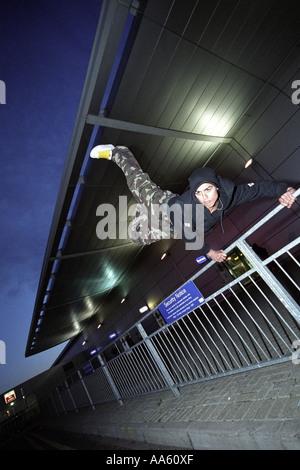 Ein Parkour-Freerunning-Athlet Voltigieren über eine Schiene - Stockfoto
