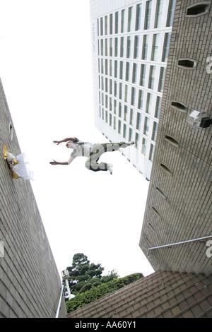 Ein Parkour-Freerunning-Sportler springen zwischen den Mauern der Stadt. - Stockfoto