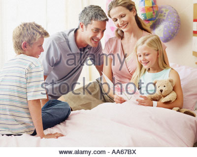Mädchen mit Eltern und Bruder im Krankenzimmer - Stockfoto