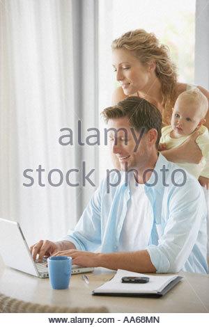 Mann am Computer mit Frau halten baby - Stockfoto