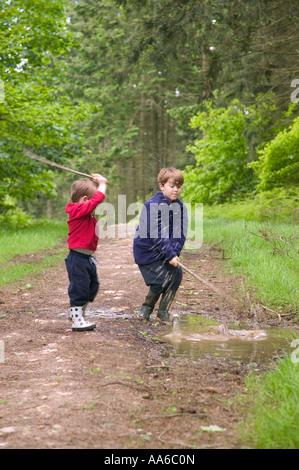 Zwei junge Brüder Spaß Spritzwasser in einer schlammigen Pfütze - Stockfoto