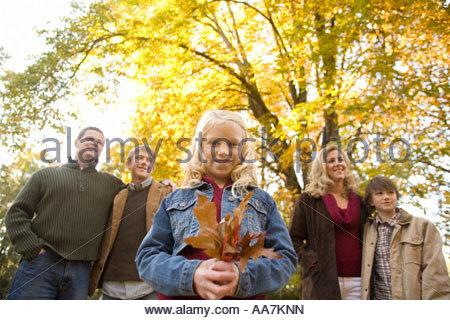 Mädchen mit Herbstlaub mit Familie - Stockfoto