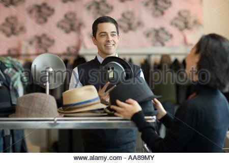 Verkäuferin helfen, Mann mit Hut - Stockfoto