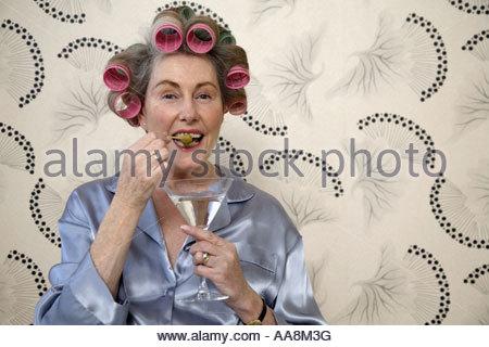 Ältere Frau Essen Olive von Martini mit Haar in Lockenwicklern - Stockfoto