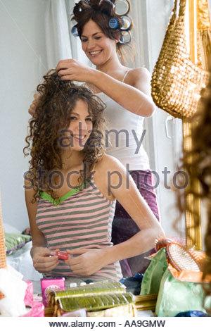 Junge Frauen, Haar-styling in Rollen - Stockfoto