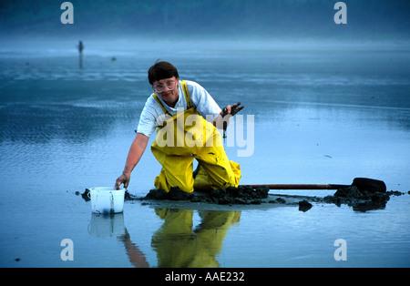 Frau Futter für Pacific Muscheln auf Long Beach, Tofino auf Vancouver Island, BC am frühen Morgen schaut in die - Stockfoto
