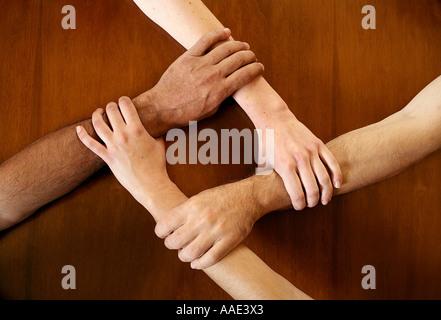 Vier Arme an den Handgelenken zusammen gesperrt - Stockfoto