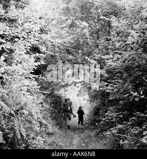 Ein Mann begleitet ein Kind mit ihrem Bruder auf dem Rücken durch einen Wald in Hampshire, UK. - Stockfoto