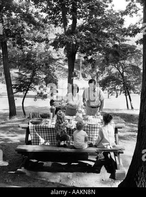 1960S 1970S FAMILIE VON FÜNF AT IM PARK UNTER DEN BÄUMEN, DIE PICKNICK-TISCH - Stockfoto