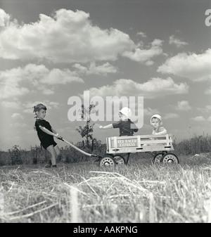 1950ER JAHREN KLEINER JUNGE ZIEHEN ROTE RACER EXPRESS WAGEN MIT ZWEI KLEINKINDER REITEN IM INNEREN - Stockfoto