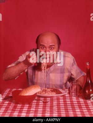 1960ER JAHREN GLATZKOPF ESSEN SPAGHETTI BLICK IN DIE KAMERA - Stockfoto