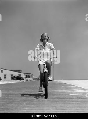 1940ER JAHRE SOMMERZEIT LÄCHELND BLONDE FRAU REITEN FAHRRAD AM STRAND STRANDPROMENADE BLICK DIREKT IN DIE KAMERA - Stockfoto