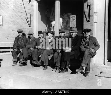 1920S 1930S GRUPPE VON ALTEN MÄNNERN IN HÜTE & LATZHOSEN SITZT AUF DER BANK VOR SCHAUFENSTER BLICK IN DIE KAMERA - Stockfoto
