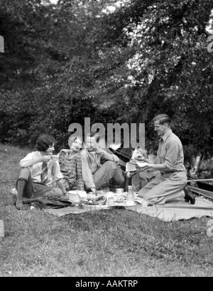 1920ER JAHREN VIER PERSONEN ZWEI PAARE MÄNNER FRAUEN SITZEN AM BODEN EIN PICKNICK - Stockfoto