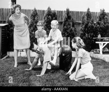 1960ER JAHRE 5-KÖPFIGE FAMILIE IM HINTERHOF PAPA GEBEN PIGGYBACK FAHRTEN FÜR KINDER - Stockfoto
