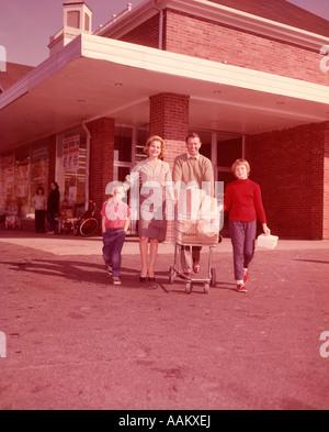1960ER JAHRE FAMILIE SCHIEBEN EINKAUFSWAGEN VERLASSEN SUPERMARKT BLICK IN DIE KAMERA - Stockfoto