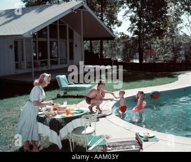 1950ER JAHRE FAMILIE 4 HINTERHOF SCHWIMMBAD HAUS MUTTER SERVIEREN ESSEN MAHLZEIT AM TISCH VON GRILL VATER JUNGE - Stockfoto
