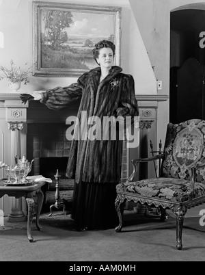 1940ER JAHREN FRAU IN FORMALEN WOHNZIMMER KAMIN TRAGEN IN VOLLER LÄNGE FELL BLICK IN DIE KAMERA STEHEND - Stockfoto