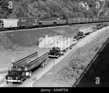 1950ER JAHRE LINIE DER VERKEHR MIT VIELEN LKW & AUTOS & GÜTERZUG VORBEI AM ANGRENZENDEN HANG - Stockfoto