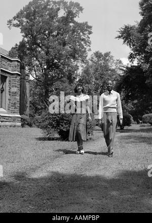 1940S 1950S AFRICAN AMERICAN COLLEGE PAAR ZU FUß AUF DEM CAMPUS TRAGEN BÜCHER - Stockfoto