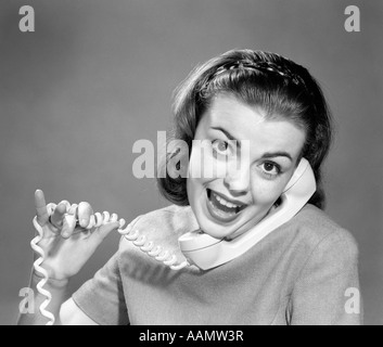 1950S 1960S JUNGE FRAU AM TELEFONKABEL IN BLICK IN DIE KAMERA FINGER GEWICKELT - Stockfoto