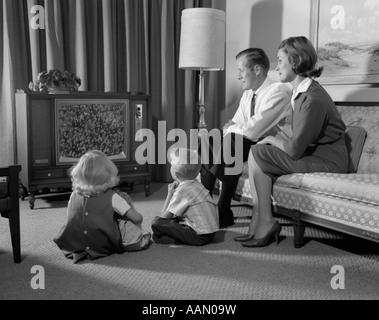 1960ER JAHRE FAMILIE SITZEN VIER IM WOHNZIMMER ANSCHAUEN FERNSEHEN MAMA PAPA AUF COUCH JUNGE MÄDCHEN AUF BODEN - Stockfoto
