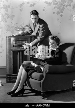 1930S 1940S FAMILIE RADIOHÖREN WÄHREND MUTTER LIEST BUCH FÜR KLEINE MÄDCHEN AUF DEM SCHOß SITZEN IM SESSEL - Stockfoto