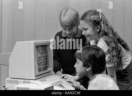 1980ER JAHRE JUNGE SITZT VOR COMPUTER SPIELEN JUNGE & MÄDCHEN AUF ÜBER SEINE SCHULTER BLICKEND - Stockfoto