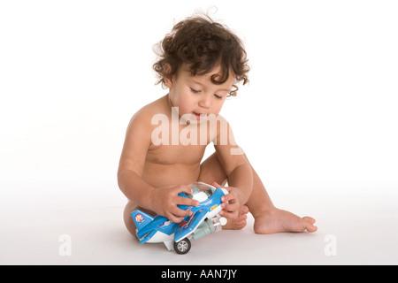 Kleiner Junge spielt mit Spielzeugflugzeug auf dem Boden - Stockfoto