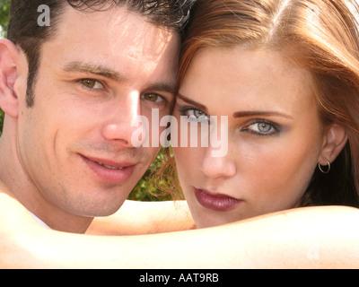 zeitgenössische Nahaufnahme Portrait jungen kaukasischen paar umarmen einander zärtlich lächelnd - Stockfoto
