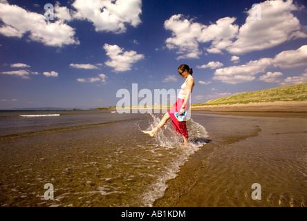 Frau am Strand tragen Flip flops bei Ebbe planschen in den Wellen - Stockfoto