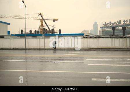 Ein Mann steht auf einem Pflaster im Regen halten einen Regenschirm in Shanghai - Stockfoto