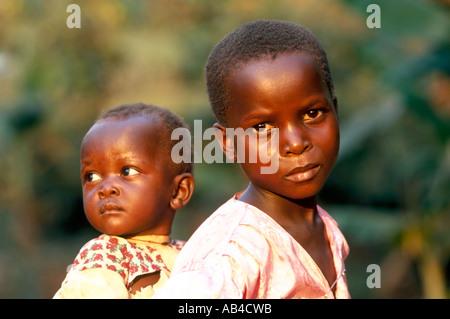 Traurig aussehende junge Teenager einheimisches Mädchen ein Baby auf dem Rücken tragen. - Stockfoto