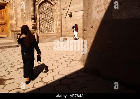 Eine Dame, die zu Fuß in die alten Viertel von Kashgar in China - Stockfoto