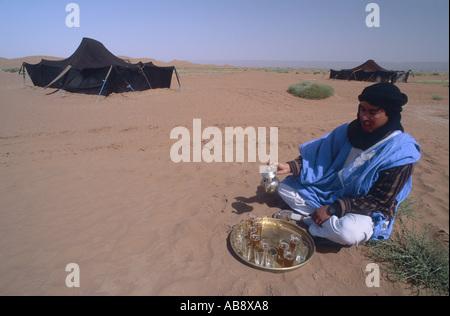 Beduinen Tee in der Wüste, sitzt im Sand vor silbernen Tablett servieren Gläser aus einer Teekanne, Marokko, South - Stockfoto