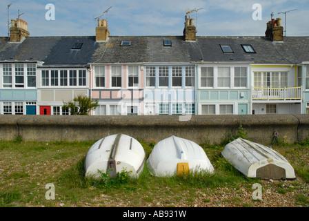 Reihenhaus direkt am Meer Ferienhäuser mit drei weißen umgedrehten Ruderboote und Deich im Vordergrund, Whitstable, - Stockfoto