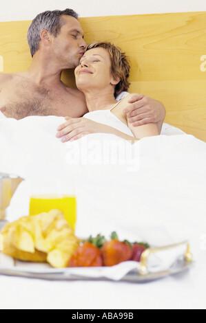 Mann und Frau im Bett zu frühstücken - Stockfoto