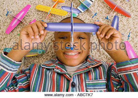 Junge liegend am Boden im Innenbereich spielen mit Spielzeug Flugzeuge - Stockfoto