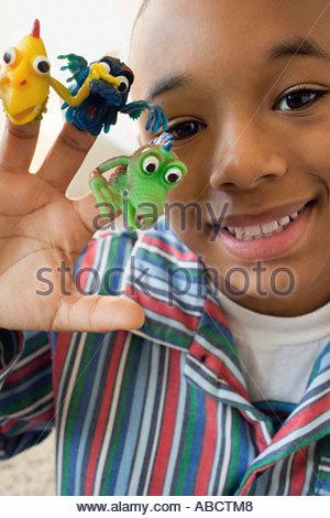 Junge im Innenbereich mit Monster Fingerpuppen an Fingern - Stockfoto