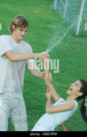 Junge Freunde spielen mit Gartenschlauch, nass - Stockfoto