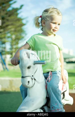 Mädchen auf Spielplatz Schaukelpferd, wegschauen - Stockfoto