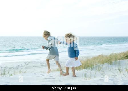 Schwester und Bruder, die Hand in Hand am Strand - Stockfoto
