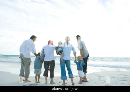 Drei Generationen Familie stehen am Strand - Stockfoto